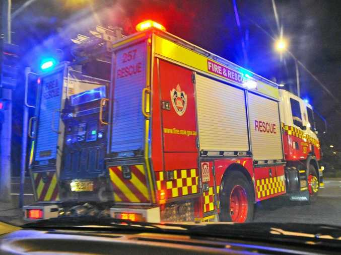 A NSW Fire and Rescue truck goes through lights with sirens blaring at night in response to a call. Photo: Rob Wright / The Coffs Coast Advocate