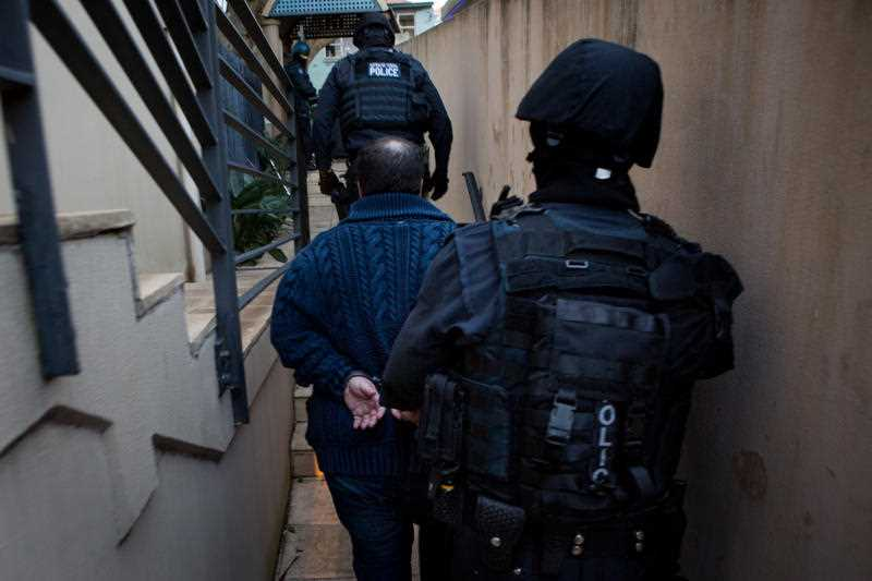 Unnamed man arrested in Sydney by Australian Federal Police. The AFP have disrupted two inter-related crime syndicates that were allegedly transporting large amounts of MDMA, cocaine and ice between Australia, Dubai and the Netherlands.