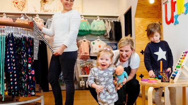 Shopping nanny Claire McLaughlin plays with Madeline Owens, 4, and sister Holly, 2, while mum Jacqui Owens shops. Picture: Jonathan Ng