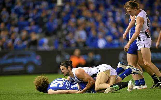 Brodie Grundy of the Magpies (second from left) tackles Ben Brown of the Kangaroos.