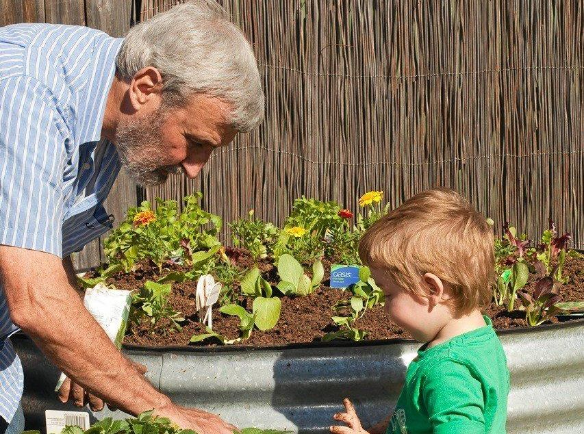 SPRING WITH DON BURKE: Don with grandson Joshua, 3, planting a flower and vegie garden in tank raised garden beds that don't take up a lot of space, but can still produce plenty of fruit and vegetables.