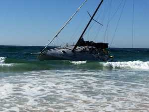 PHOTOS: Race to rescue yacht caught on reef near Byron Bay