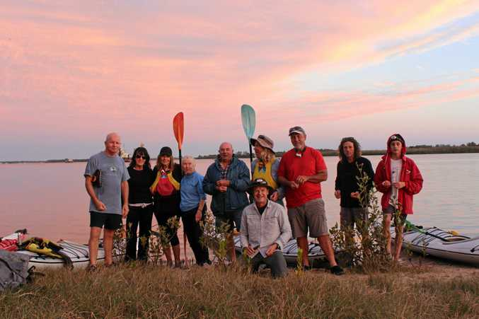 REST STOP: The group on this month's moonlight paddle takes a quick break to recharge and soak up the colourful sunset on the bank of the Clarence River.