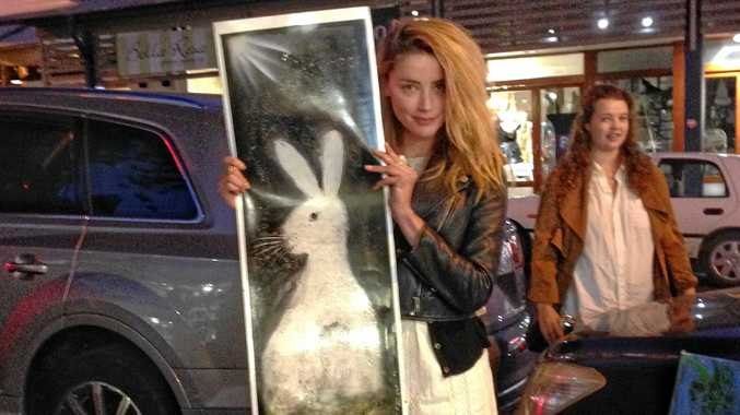 SWEET GIFT: Actress Amber Heard with the  picture of Sugar the rabbit given to her by Byron Bay street artist, Aboozar 'Nima' Jamishi.