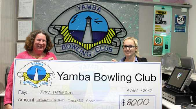 THRILLED: Judy Patterson is presented a cheque by Zoe Collier (right) who drew  Ms Patterson's member number.