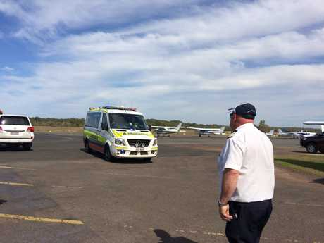 An ambulance leaves the scene of the light plane crash at Caloundra Airport with two injured people on board.