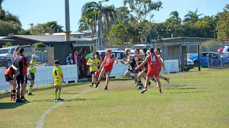 Eastern Swans' Shane Martin kicks the ball out of bounds under Saints pressure.