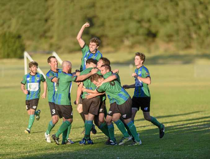 Maclean Bobcats teammates swamp Mackenzie Allen after he scored a last-minute winner for Maclean against Urunga.