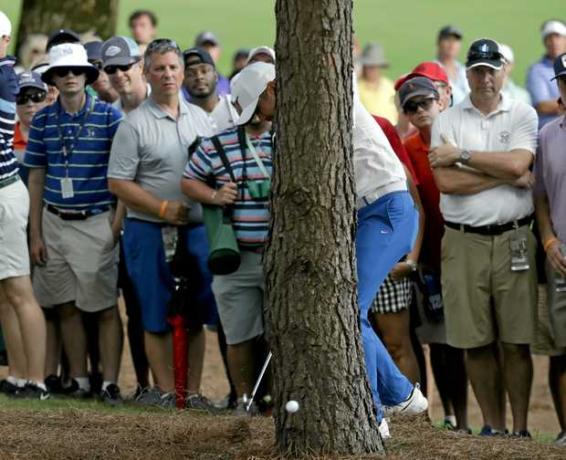 Jason Day of Australia, hits from behind a tree on the 18th hole during the third round of the PGA Championship golf tournament at the Quail Hollow Club.
