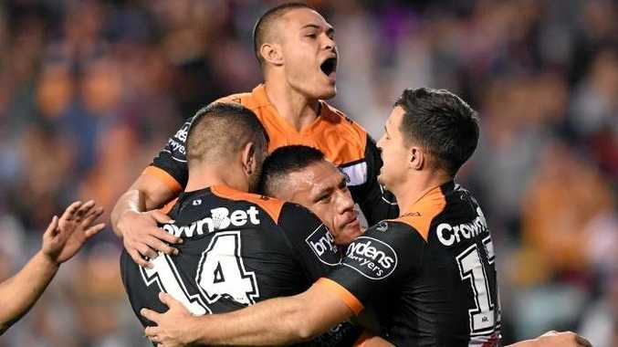 Sauaso Sue (centre) of the Tigers is congratulated after scoring a try. Photo: AAP