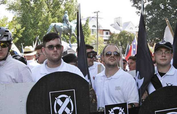 James Alex Fields Jr., second from left, holds a black shield in Charlottesville, Va., where a white supremacist rally took place. Fields was later charged with second-degree murder and other counts after authorities say he plowed a car into a crowd of people protesting the white nationalist rally. (Alan Goffinski AP)