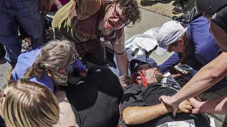First responders work with victims at the scene where a man identified by police as James Alex Fields Jr., allegedly drove a car into a crowd of people who had gathered to protest a white supremacist rally (Go Nakamura via AP)