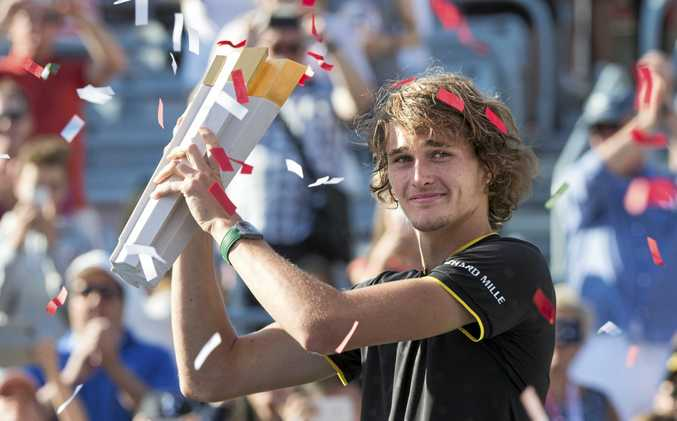 Alexander Zverev, of Germany, holds up the winner's trophy after defeating Roger Federer, of Switzerland, in the final at the Rogers Cup tennis tournament in Montreal