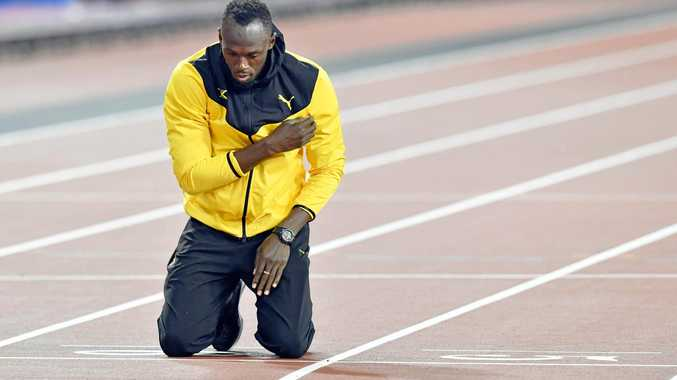 Usain Bolt kneels at the finish line during his retirement ceremony following the World Athletics Championships in London