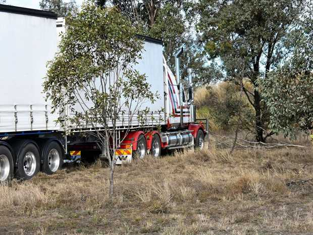 TRUCK CRASH: A truck cut across the Warrego Hwy and a paddock before stopping in front of a dam wall.