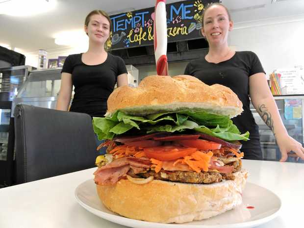 Tempt Me Cafe and Pizzeria owner Samantha Kean and daughter Chloe with the Maryborough Monster - a burger on a cob bun with the lot including cheese, which can feed a family of four.