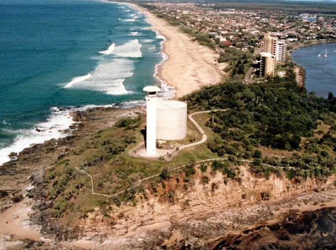 Aerial view of the coastline looking south from the Point Cartwright headland showing the lighthouse and water tower in foreground, 1985.