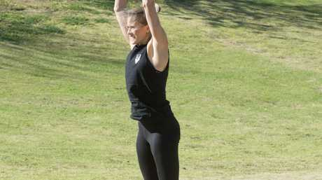 Burpee step three: Flick those legs back underneath you into a low squat and then jump into the air with hands raised.
