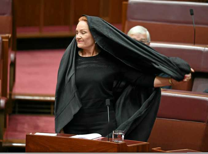 One Nation Senator Pauline Hanson takes off a burqa during Senate Question Time at Parliament House in Canberra, Thursday, August 17, 2017.