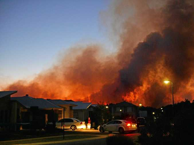 A fire threatens homes in Aura. Residents evacuate.