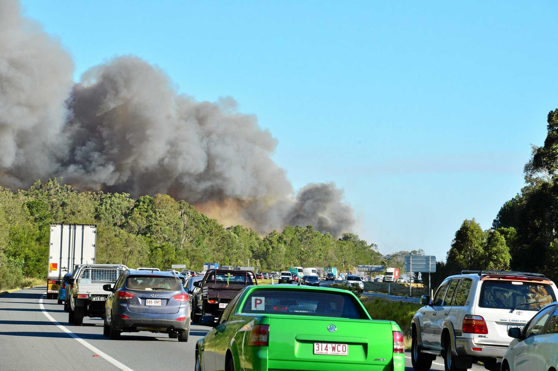 A fire threatens Aura . Residents evacuate. South bound traffic on the Bruce highway slows to a crawl. water bombers fight the fire.