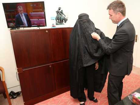 Pauline Hanson's chief-of-staff James Ashby assists her with the burqa. Picture: Gary Ramage