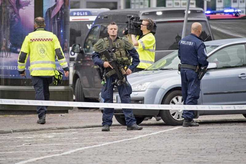 Police officers gather at the site of a multiple stabbing on the Market Square in Turku, Finland