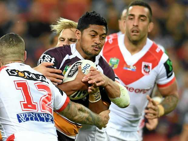 Anthony Milford of the Broncos (centre) is tackled by the Dragons defence at Suncorp Stadium.