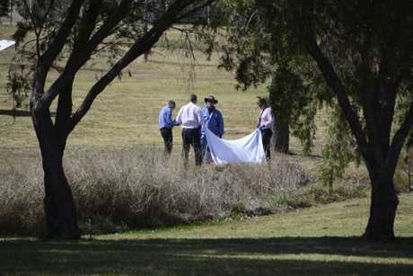 Police investigators hold up a large white sheet to cover the body of a woman found in West Creek in Kearneys Spring on August 21, 2017.