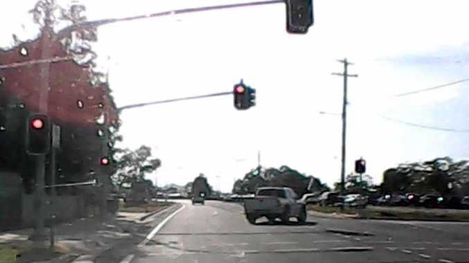 A white ute drives through a red light.