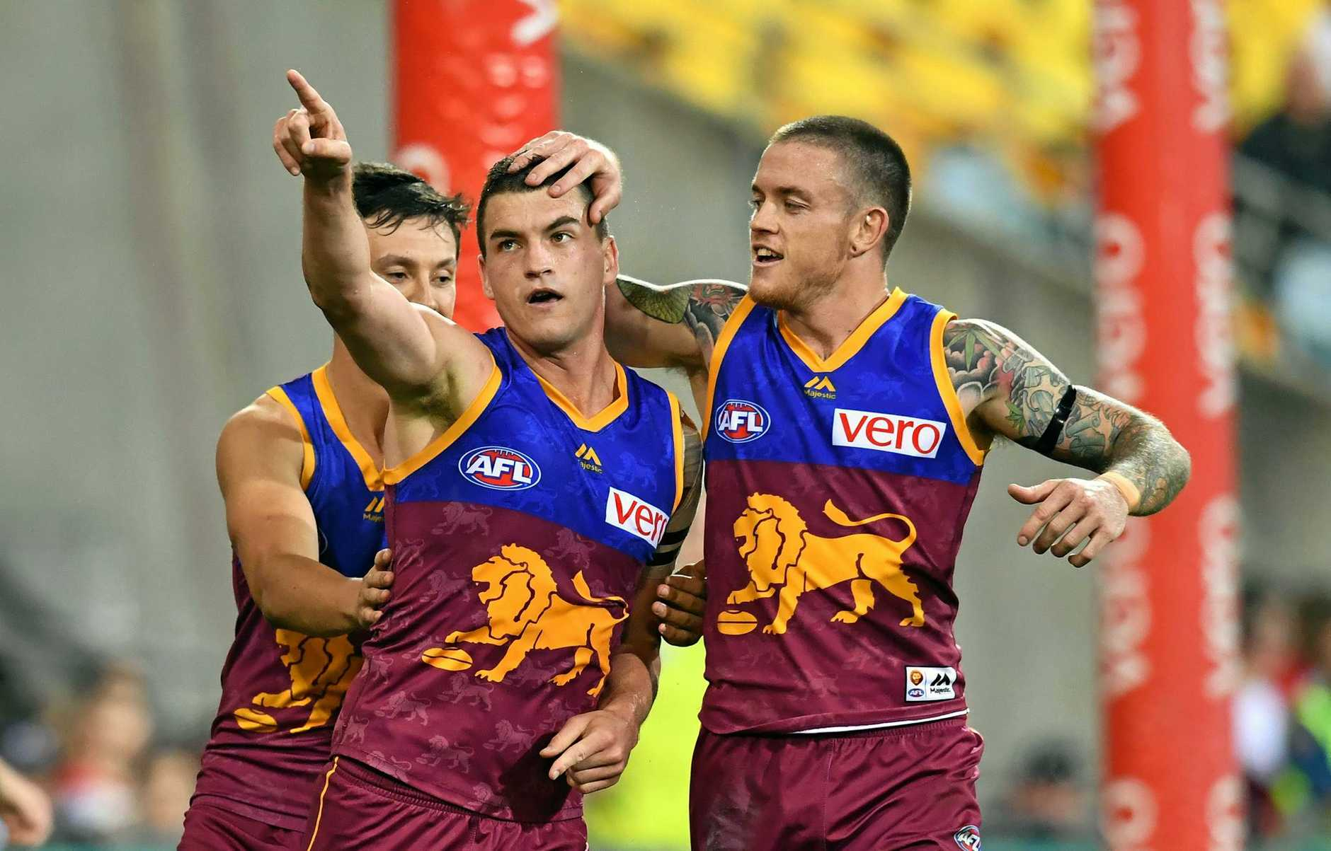 Tom Rockliff (left) of the Lions celebrates kicking a goal with Claye Beams (right)