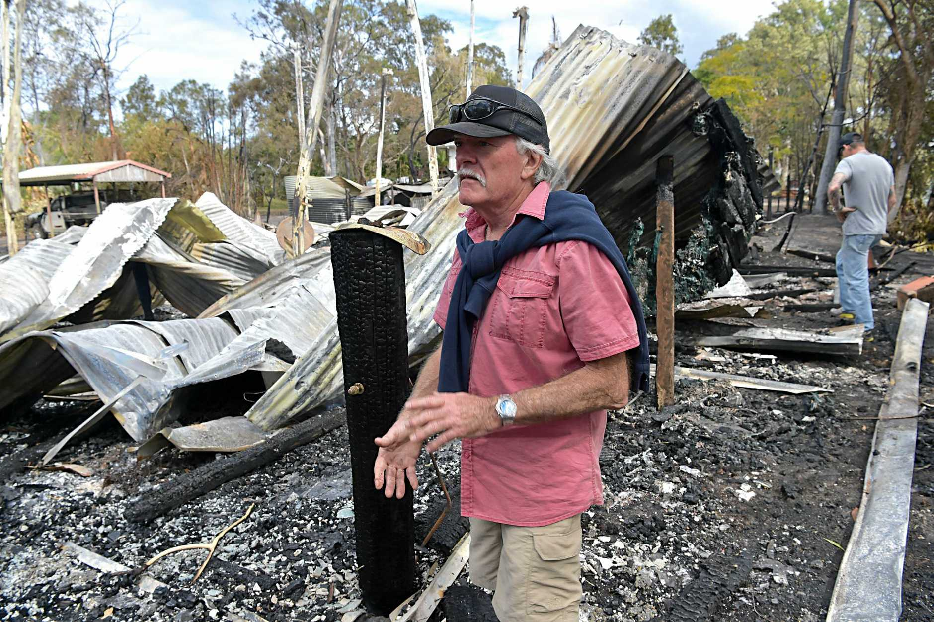 HOMES RAZED: Noosa North Shore Home owner Mike Hancock in the ruins of his house which was destroyed by fire.
