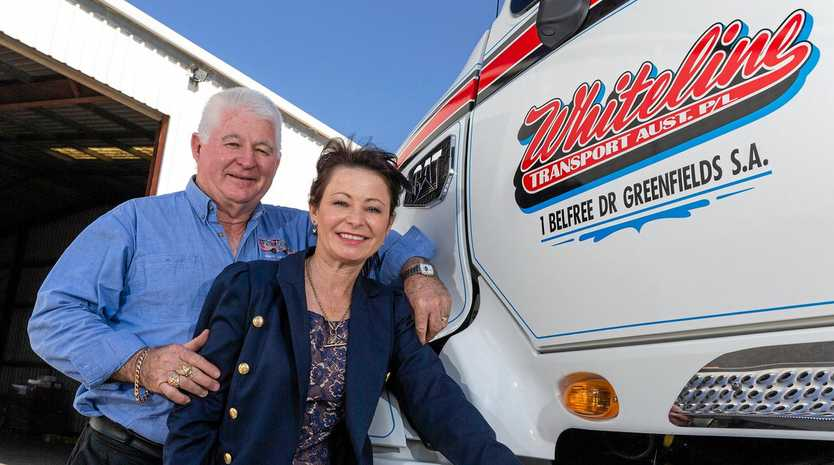 TOUGH GIG WITH BIG RIGS: Bob and Sharon Middleton with a Whiteline Cat Truck at their South Australian headquarters.