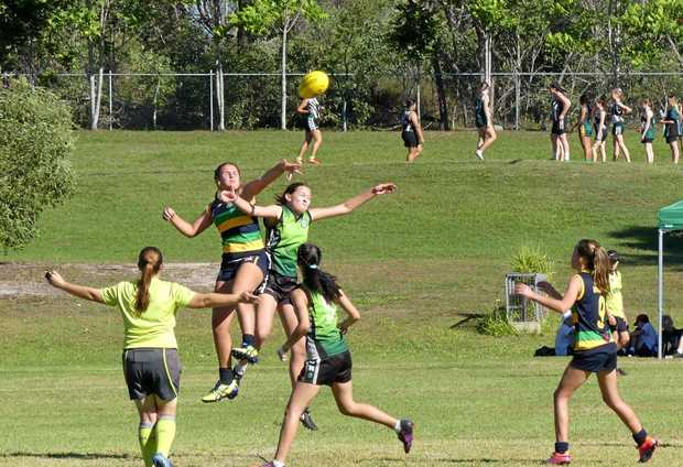 SPORTING DREAMS: Mackenzie Brinin (centre left), 14, has loved every minute of Aussie Rules football since she made the move.