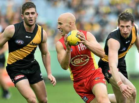 Gary Ablett of the Suns (centre) is pursued by Anthony Miles (left) and Dylan Grimes of the Tigers.
