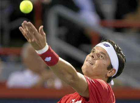 Milos Raonic of Canada tosses the ball to serve.