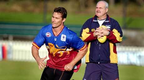 Lions coach Leigh Matthews keeps a close eye on Alastair Lynch during a training session