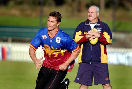 Lions coach Leigh Matthews keeps a close eye on Alastair Lynch during a training session