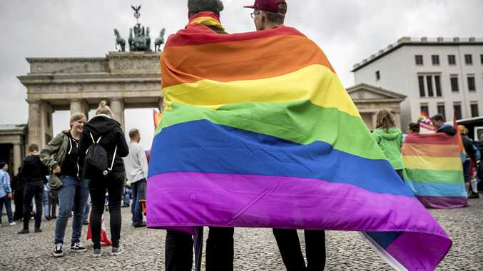 Men with rainbow flags celebrate the legalisation of same-sex marriage in Berlin.