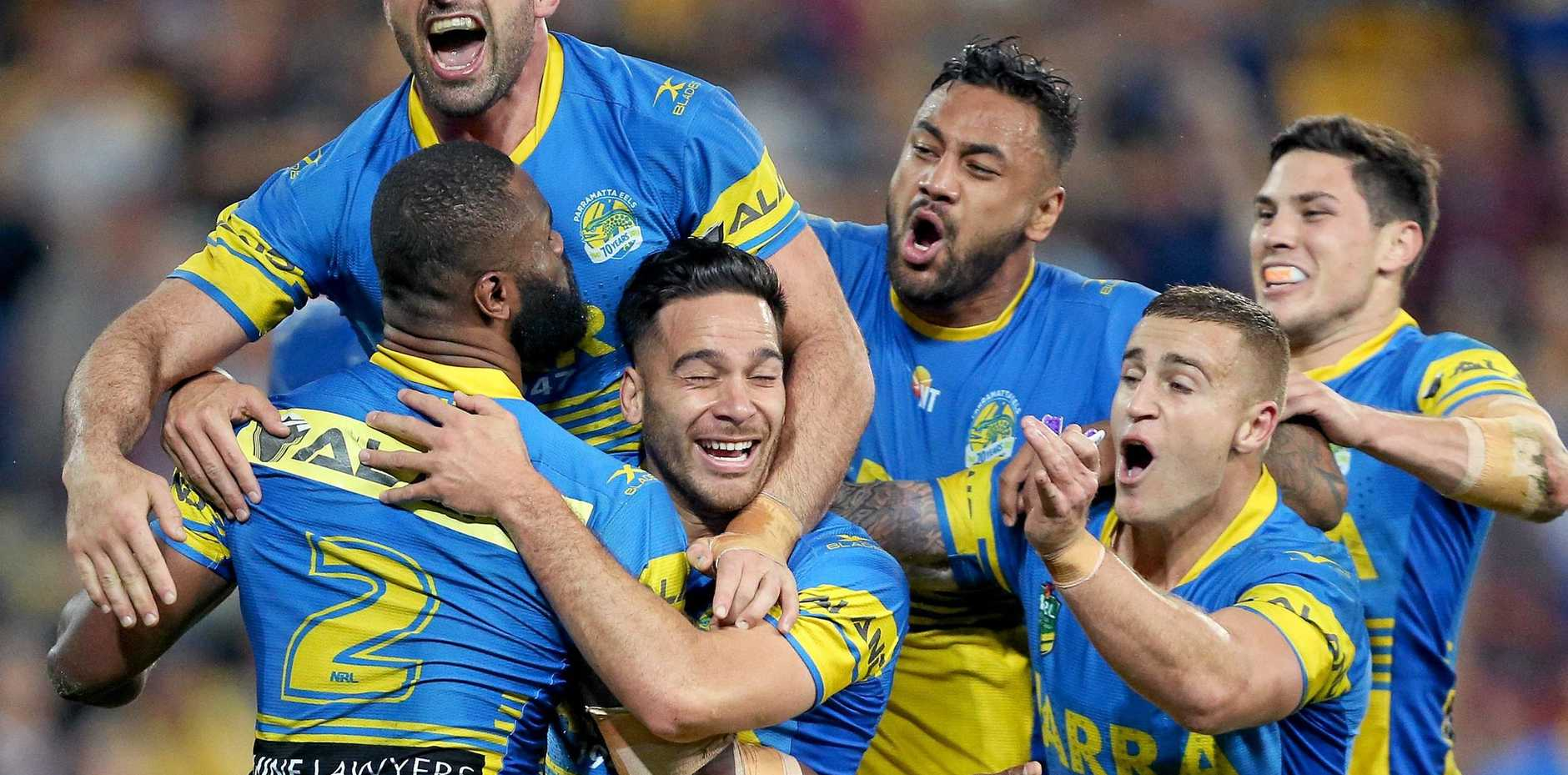 Corey Norman of Parramatta (centre) celebrates with teammates after scoring a try.