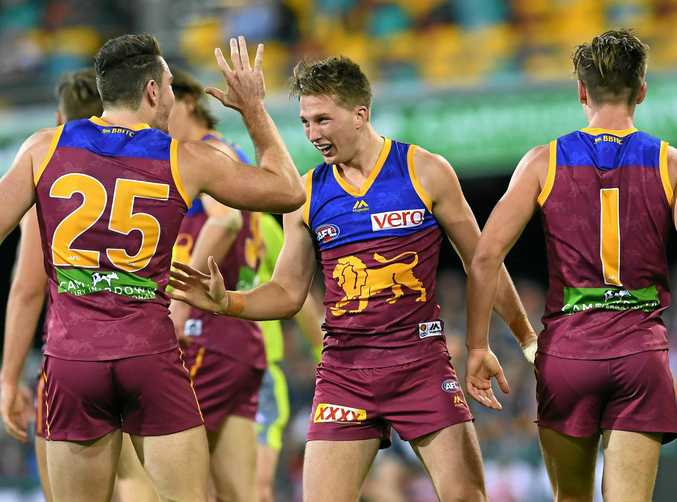 Alex Witherden of the Lions (centre) celebrates scoring his first goal in round 18.