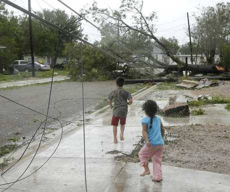 Children walk near downed power lines and fallen trees left in the aftermath of Hurricane Harvey Saturday, Aug. 26, 2017, in Victoria, Texas. (AP Photo/Charlie Riedel)