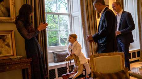 In this hand out photo released by Kensington Palace, Britain's Prince George, centre, talks to Kate, the Duchess of Cambridge after meeting US President Barack Obama, second right, and first lady Michelle Obama, at Kensington Palace.