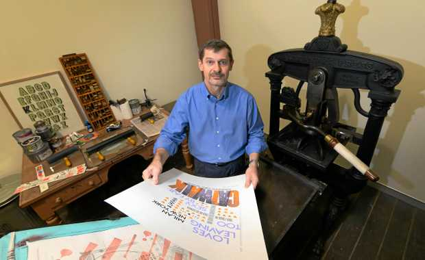 Derek Lamb with the old press used to produce his fashion inspired posters now on display at the Rockhampton Art Gallery.