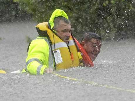 Wilford Martinez, right, is rescued from his flooded car by Harris County Sheriff's Department Richard Wagner along Interstate 610 in floodwaters from Tropical Storm Harvey on Sunday, Aug. 27, 2017, in Houston, Texas.