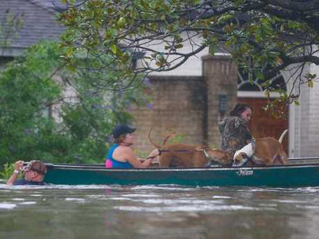 A family evacuates their Meyerland home in Houston, Sunday, Aug. 27, 2017. Rescuers answered hundreds of calls for help Sunday as floodwaters from the remnants of Hurricane Harvey rose high enough to begin filling second-story homes, and authorities urged stranded families to seek refuge on their rooftops.