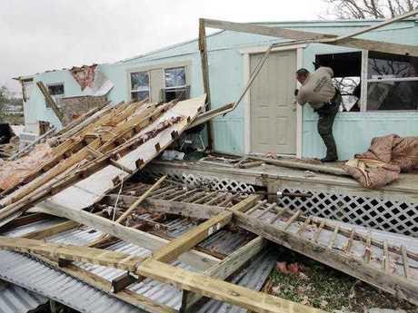 An official climbs through a window as he checks home damaged by Hurricane Harvey, Sunday, Aug. 27, 2017, in Rockport, Texas.