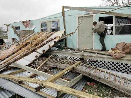 An official climbs through a window as he checks home damaged by Hurricane Harvey, Sunday, Aug. 27, 2017, in Rockport, Texas.