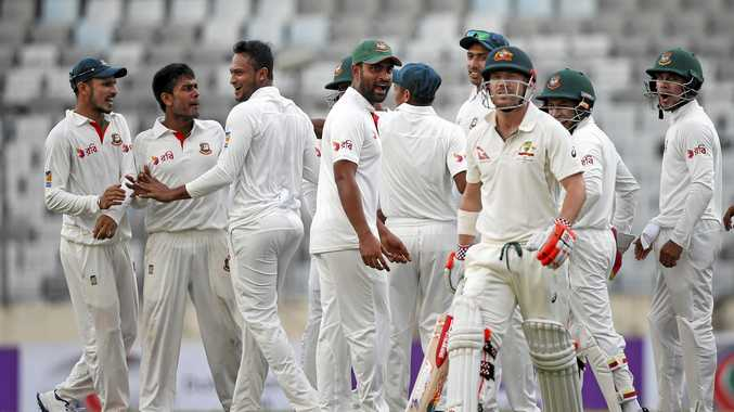 Banglades's Mehedi Hasan Miraz, second left, celebrates with his teammates after the dismissal of Australia's David Warner.