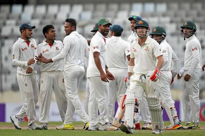 Banglades's Mehedi Hasan Miraz, second left, celebrates with his teammates after the dismissal of Australia's David Warner.